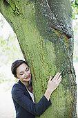 Businesswoman hugging tree