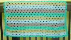 Shell stitches in beachy-hues make this crochet baby blanket a summertime favorite!