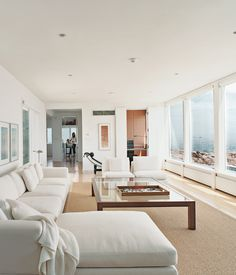 In the living room, there's a black leather Le Corbusier lounge and a Minotti sofa set, wall to wall windows & ocean view.