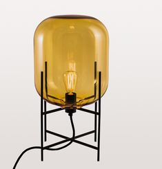 A warm statement table or small floor lamp in stunning amber yellow on black stand. The hand blown glass made in Murano, Italy balances on a simple