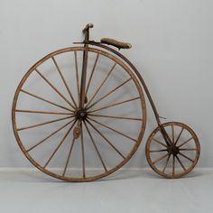A VELOCIPEDE Late 19th century. Stomme och slipbanor av smidesjärn, handtag och hjul av trä. Stoppad sadel. Framhjulets diameter 122, bakhjulets diameter 54, längd ca 170, total höjd 142 cm. Estimate: 10 000 SEK