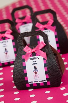 Personalised Hen Party favours  Each box contains a lovely heart shaped silver colour wine glass charm with acrylic beads. The little handbag shaped favour box is personalised with the name of the Hen and date of the party and embellished with a satin bow. Boxes are available in Black or white with either black and red or hot pink contrast.  Picture shows Hot Pink Sex in the city design.   For further details and to view full range of matching products please visit www.personal-e-yours.co.uk