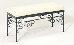 Una panca in ferro battuto con cuscino bianco, ideale per arredare il terrazzo.