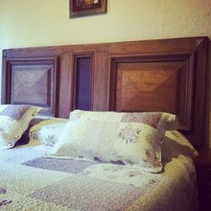 Respaldo de cama realizado con dos puerta de roble reciclada y con apliques en chapa oxidada
