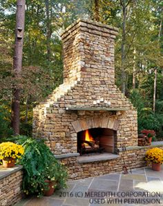 Create a focal point with a large stone fireplace. This one features rough field stone, which gives it a rustic look that fits well with the wooded setting. Ledges mark the edge of this outdoor room and offer guests a place to sit and enjoy the fire. Fabulous Outdoor Fireplace Designs - Bhgrelife.com