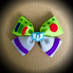 Toy Story Character Inspired Buzz Lightyear Disney Pixar Hair Bow Green and Grey Grosgrain Ribbon Decorated with Felt Accents, rhinestones and space ranger centrepiece. Mounted on an alligator clip. I can do custom bows, just let me know if youd like something specific. Price is for single bow.