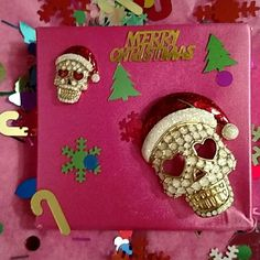 "BJ MATCHING SKELETON SANTA PINS. PRETTY BETSEY JOHNSON HOLIDAY SET OF SKULL HEAD MATCHING  ""PINS"" ADORNED WITH A RED SANTA HAT, WHITE BALL AT THE TIP, HEART SHAPED EYE OPENINGS, AND  AN OPEN MOUTH FULL OF GOLD TEETH. BEAUTY IS IN THE EYE OF THE BEHOLDER. YOU ARE SURE TO GET SOME LOOKS AROUND THE HOLIDAY. THE LARGE PIN HAS A REGULAR PIN BACKING AND THE SMALL PIN HAS A TIE TACK BACK.  WITH BLING AND VERY UNUSUAL.....                               BE THE FIRST IN YOUR NEIGHBORHOOD TO WEAR THESE…"