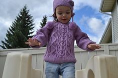 """This heirloom quality sweater uses twisted cables, bobbles and chain stitches. The hat has three pompoms, one on top and two on sides, has attached neck warmer on the back and a heart of chain stitches on the side. This is for 2- to 4-years olds; however, it can be easily transformed for young girls. Finished chest size is 23"""" ~ 25""""."""