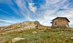 Hike or ride from Charlotte Pass to the summit of Mount Kosciuszko, through the peaks of Kosciuszko National Park. Set out along the old road to Mount Hut Images, Mountain Bike Trails, Free Park, Visit Australia, Snowy Mountains, Trip Planning, Wild Flowers, Places To See