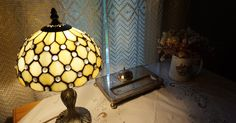 kuvia keltaiseta kamarista, tiffanytyyppinen lamppu, kuivakukkia, perhostauluja, vanhoja matkalaukkuja ja vanha maapallo.