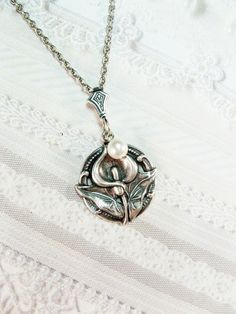 White Calla Lilly necklace. So pretty! Even has a pearl! JAK is the only person I can ever picture in pearls. She would love this!