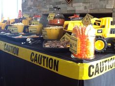 Table setup  black dollar store shower curtain, some trucks from the toy box, yellow paper around containers or yellow spray pain t on coffee cans'   and the caution tape  dollar store cheap!!!