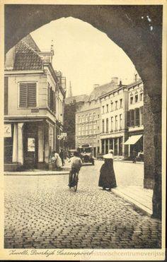 Gezicht in de Sassenstraat vanonder de Sassenpoort, ca. 1935. Een vrouw in klederdracht steekt de straat over. Bij de schoenenhandel van E. Anhalt, op de hoek van de Sassenstraat en de Koestraat worden de ramen gewassen. Naast de slagerij van E. Keizer, op de hoek van de Schoutensteeg, staat de fiets klaar, waarmee de bestellingen werden bezorgd. Zwolle kaart #Overijssel #Salland