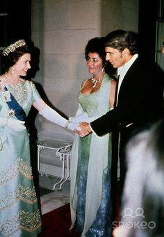 Her Majesty, Queen Elizabeth shaking John Warner's hand at a White House State Dinner. His wife, Elizabeth Taylor looks on.