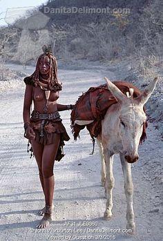 Himba woman, Angola . She drives home her donkey along dusty white tracks.