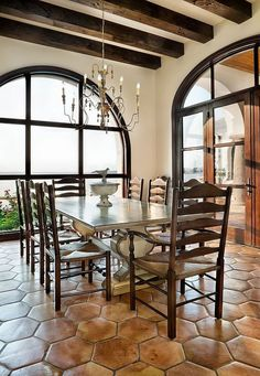 Spanish style dining room with exposed beams and terracotta tile