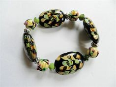 This handmade chunky stretch lampwork bracelet has oval black lampwork beads with swirled green and beige designs.    There are also green opaque crystals, pewter spacer findings scattered throughout the bracelet and round beige lamp work beads with a raised design.    The oval beads measure 1 1/4 x 7/8.  The bracelet measures about 7 3/4 - 8 before stretching.   This is a one of a kind lampwork glass bead bracelet. I did not make the beads. I only designed and made the bracele...
