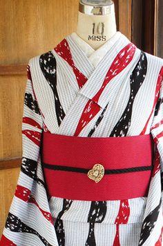 お花のような細かな模様がアクセントになった白の地に、赤と黒の立涌縞が染め出されたレトロモダンな浴衣です。