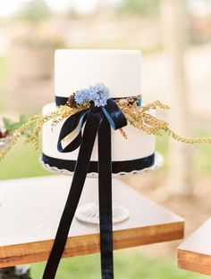 Navy ribbon-tied wedding cake: http://www.stylemepretty.com/little-black-book-blog/2016/02/02/glamorous-western-wedding-inspiration-at-brush-creek-ranch/ | Photography: Lisa O'Dwyer - http://www.lisaodwyer.com/