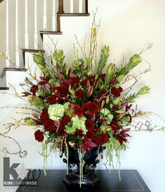 Large arrangements like this one are really engrossing. Here we have burgundy lilies, leucodendron, hydrangea, roses, kiwi branches, hanging amaranthus, burgundy roses, and forsythia.