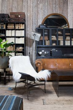 Cozy leather chair with shearling throw, dark details and vintage sofa. Interior inspiration. http://bdantiques.com/
