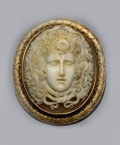 A Victorian shell cameo brooch.  The shell cameo depicting the mask of Medusa, with wings in her hair and entwined serpents, within ropetwist decorated mount