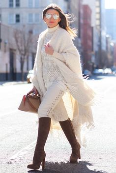 Street Style - The Top Blogger Looks Of The Week: Fashion blogger 'Lovely Pepa' wearing an ivory fringe cape, an ivory turtleneck sweater, a white lace fringe tunic, ivory lace-up skinny jeans, brown suede heeled over the knee boots, mirror sunglasses and a brown handbag