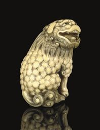 An ivory Netsuke of a Shishi, Signed Masayume, late 19th Century well detailed, it sits on its haunches, its head turned towards the right with an expression of happy anticipation, eyes inlaid -- 2 3/8in. (6cm.) high