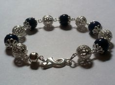 Child Abuse Awareness Bracelet ; A 7 1/2 inch bracelet made with silver filagree beads and end caps with blue stone beads, a silver awareness ribbon link and a magnetic clasp. $19.99