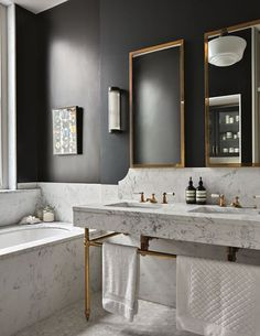 Brass Finish and Black Wall in a Marble Bathroom