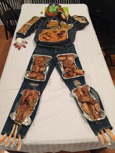 I have no website for this. But I wanted to share w/ my Pinterest friends. We did this for Halloween. Huge success. Arms = green bean casserole, stomach is taquitos and baked ziti . Heart was salsa, thighs were baked chx thighs, calves were baked chicken legs, feet were white chocolate pretzel stix. Fingers were made from a latex glove w/ hotdogs coming out the fingers.  The other hand holding the bottle to the mouth was made of dough.  The head is a pumpkin and the brain is cauliflower.