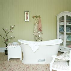 Oriental bathroom  A faux magnolia tree inspires the subtle colour scheme in this oriental-inspired bathroom. Tongue-and-groove panelling is painted eau de nil as a refreshing backdrop to a painted Martin Chadder freestanding bath. A white Belle Maison armoire stores towels, cushions and quilts, while vintage flower hooks use wall space. Soft rose in the patterned carpet, towels and orchid box frame add warmth and contrast.  Chosen by  Country Homes & Interiors