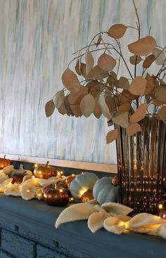 Vintage Vase with Dried Eucalyptus. Love this simple fall mantel decor with copper fairy lights, pale blue pumpkins and metallic pumpkins with cream colored DIY felt leaf garland. Beautiful and neutral fall decorating ideas. Cozy fall mantel decor inspiration. Click for more fall mantel decorating ideas and fall mantel decorations for every decor style. Fall mantel decorations with fire places. Cute and simple fall decor!