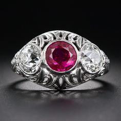 A bright red and lively faceted round ruby, weighing one-and-a-half carats, is the glistening centerpiece of this gorgeous, original Edwardian bombe' style ring three-stone ring. The beautiful bezel-set ruby is highlighted on each side by a sparkling one carat European-cut diamond also set in platinum bezels. The delicately pierced openwork features a scrolled foliate design. A superb and stunning antique ruby and diamond ring - circa 1915.