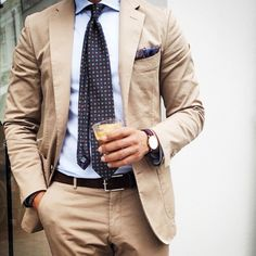 Tan suit, light blue shirt, navy tie with medallions