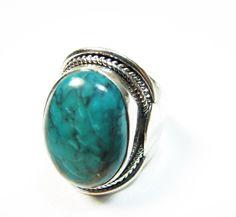 Ce bijou indien est une bague large en argent avec une pierre naturelle ovale en turquoise . C'est un bijou argent de taille 57 et sa monture est lisse avec un motif ciselé autour de la pierre. C'est une bague argent qui vient d'Inde