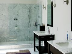 The glass shower doors in this contemporary bathroom expose the marble walls, giving the room a light, airy look. Designed by Jeanette Cataldo