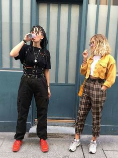 two young women* dressed in grunge fashion* one wearing a black outfit* with multiple belts and red sneakers* the other in checkered ankle trousers* white cropped top* and a cropped yellow jacket Indie Outfits, Grunge Outfits, Fashion Outfits, Womens Fashion, Fashion Styles, Black Outfits, Fashion Fashion, Girl Outfits, Trendy Fashion
