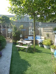In de tuin een palletbank met zelfgemaakte kussens en daarboven een kastje van pallethout dat wit geschilderd is.
