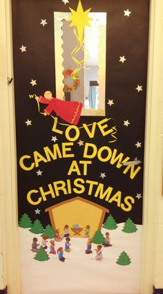 """Christmas Door- Glitter stars and an angel announcing """"Love Came Down a Christmas"""".  We took pictures of all the children """"praying"""" then cut them out and placed them around """"Baby Jesus""""."""