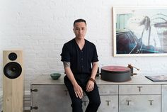 Phillip Lim in his home with record player, speaker, and old photograph