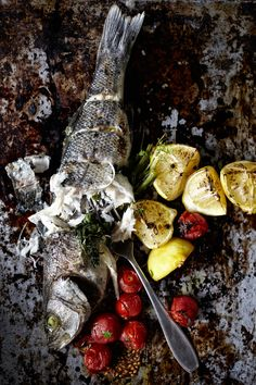 Baked sea bass, grilled lemons and tomatoes, salt and pepper.