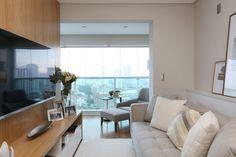 Sala de estar integrada com a varanda. Painel TV em folha de madeira natural, sofá claro, tapete, almofadas, poltrona com apoio de pés, quadros. Sala decorada, decoração. Reforma e decoracao apto completo