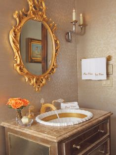 """A retrofitted 18th century French commode is the center of a powder room flaunting gold fittings and a ruffled china sink. The fixtures are 24 karat gold-plated. The hand towels are embroidered with the words """"Pour vous,"""" French for """"For you."""""""