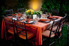 outdoor reception table setting - orange tablecloth and napkins, black chairs and plates, and a yellow, orange, and green centerpiece - photo by New Mexico based wedding photographers Twin Lens