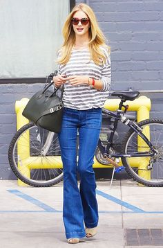 Try a pair of flared jeans with platform sandals and a striped shirt for an on-point denim look.  On Rosie Huntington-Whiteley:  ​Anine Bing Striped Loose Fit Linen T-Shirt ($129); Seafarer...