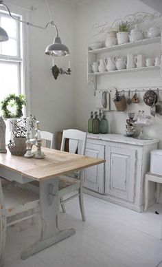 Beautiful and spare #swedishstyle in this kitchen with open shelving, pale colors, barn style pendant lights, and vintage cabinetry. #shabbychic #vintagestyle