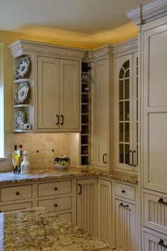 Stunning cream cabinets paired with granite countertops prove to be an excellent design choice in this sunny yellow kitchen.