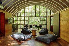 Arched roof/quonset camp, barn doors, industrial wall of windows, floor seating, green outdoors - Arca - Small House Swoon