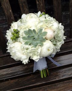 Romantic wedding bouquet with peonies, hydrangea, scabiosa, succulents, and hypericum berries.
